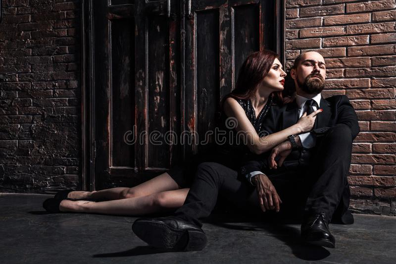 Man in suit and woman in evening dress sitting on his lap. Ginger woman looks at him and wants to kiss royalty free stock photo