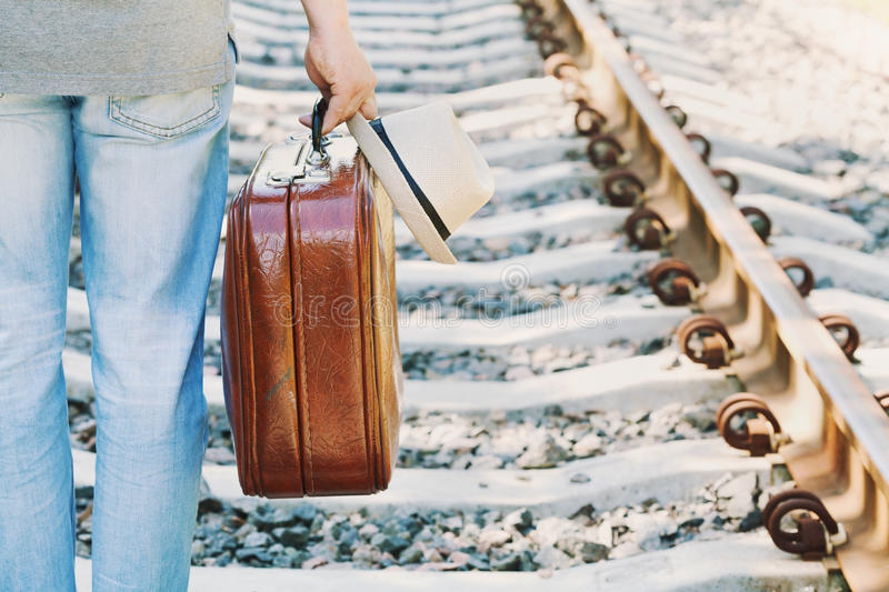 Man with suitcase and hat standing on railway on a sunny day. Holidays, vacation, travel and trip. Passenger with luggage. Man with retro suitcase and hat stock image