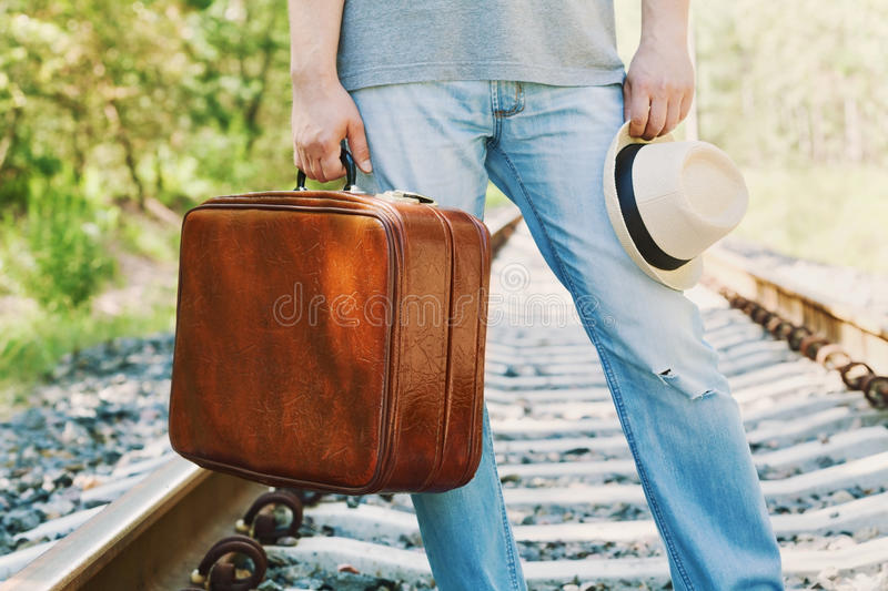 Man with suitcase and hat standing on railway on a sunny day. Holidays, vacation, travel and trip. Passenger with luggage. Man with vintage suitcase and hat stock photography