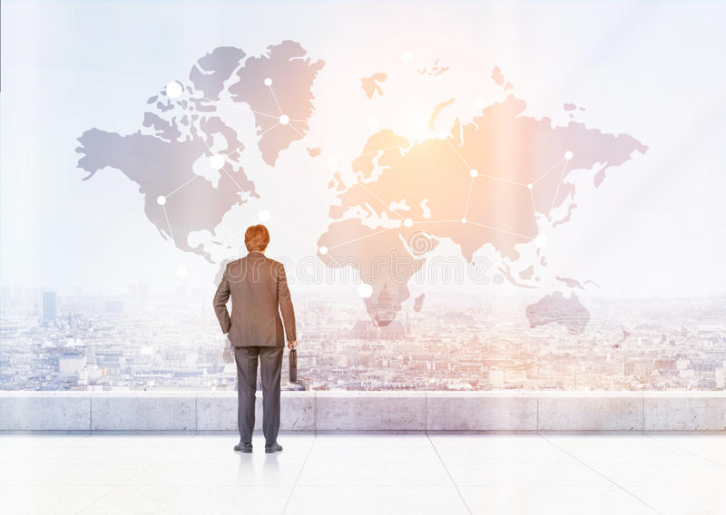 Man with suitcase is looking at world map. Rear view of businessman with suitcase looking at large world map with landmarks in the sky. Toned image. Elements of stock photo