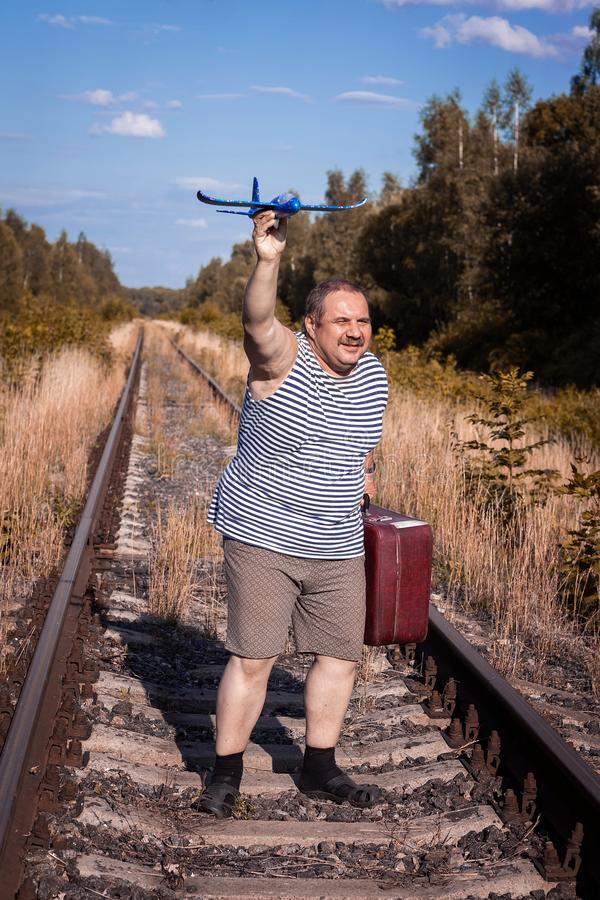 Man with suitcase rails. A man with a suitcase goes by rail and launches a toy plane into the sky stock photos