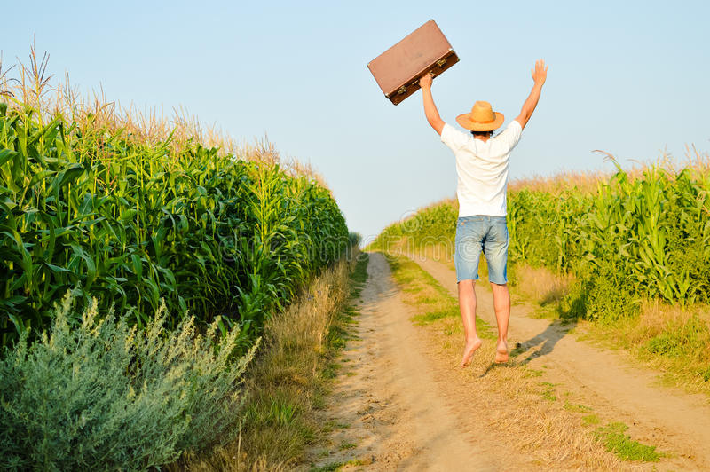 Man with a suitcase on a rural road in summer royalty free stock photography