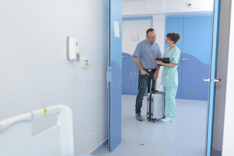 Man with suitcase talking to nurse in corridor royalty free stock photo