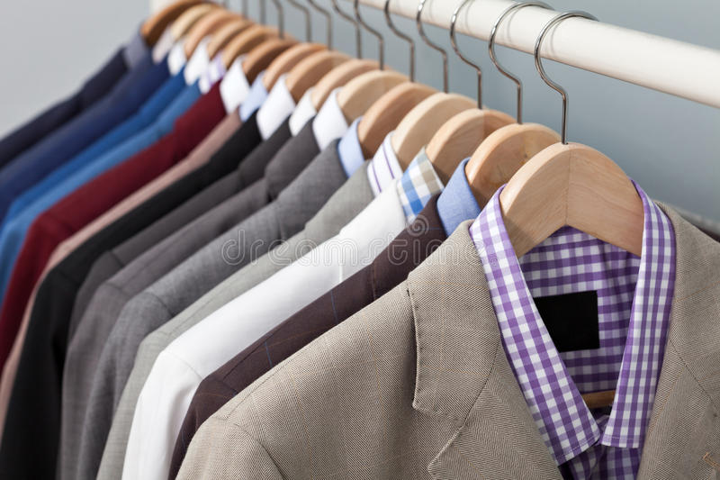 Man suits in a closet. Closeup of the upper section of a row of different coloured man suits in a closet on hangers in a store or showroom stock photos