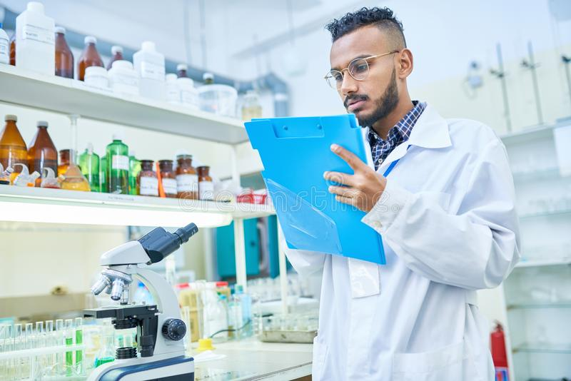 Man summarizing results of experiment in laboratory stock photography