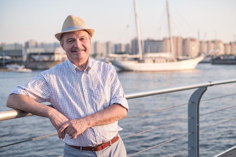 Man in summer hat standing near sea at sunny summer day. Happy mature hispanic man in summer hat standing near sea at sunny summer day royalty free stock photos