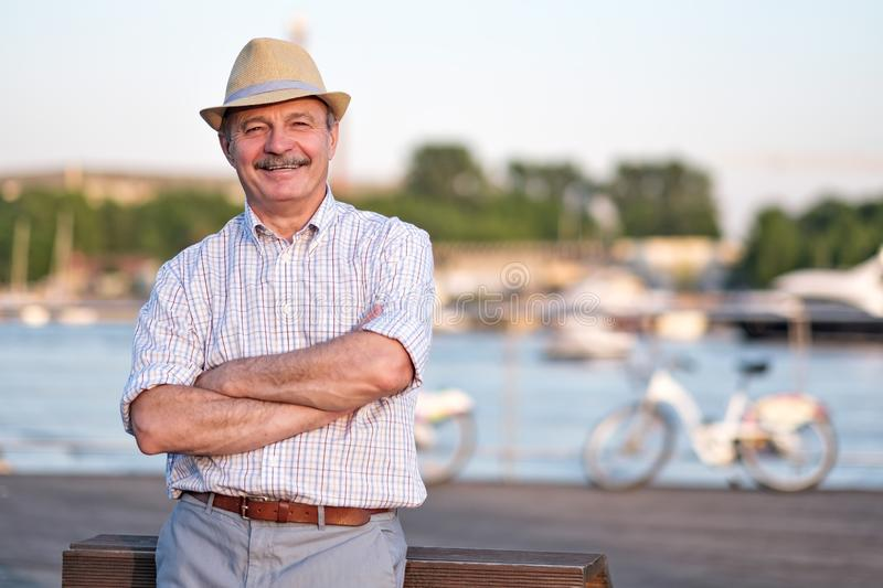 Man in summer hat standing near sea at sunny summer day. Happy mature hispanic man in summer hat standing near sea at sunny summer day stock image