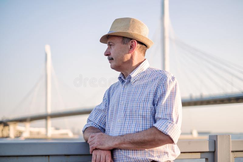 Man in summer hat standing near sea at sunny summer day. Happy mature hispanic man in summer hat thinking and looking aside near sea at sunny summer day stock photo