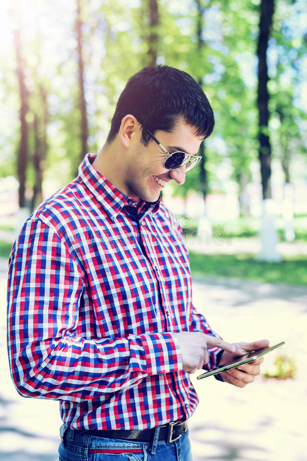 The man in the summer in the park, reading glasses, looking a map and news feed on social networks, happy smiles. Watching a video film in jeans bright sunny royalty free stock images