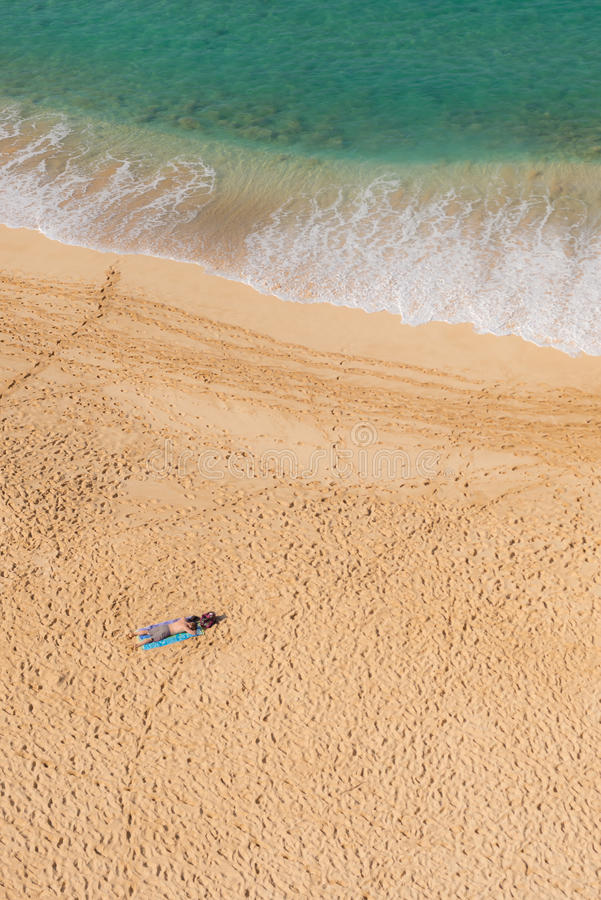 Man sun bathing solo on secluded beach