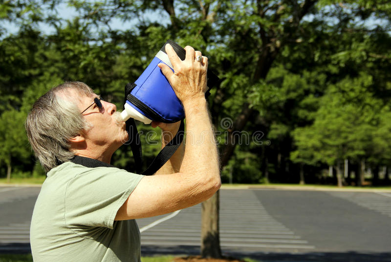 Man in the sun takes a drink to hydrate. Man in the hot summer sunshine takes a drink of water to quench his thirst and hydrate himself stock images
