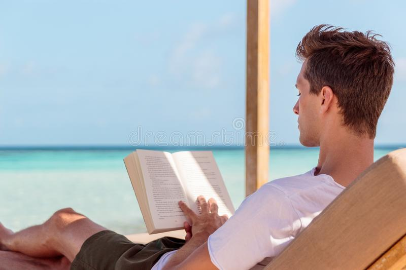 Man on a sunchair reading a book in a tropical location. Clear turquoise water as background. Boy in t shirt and swimsuit reading a book during holiday in the royalty free stock photo