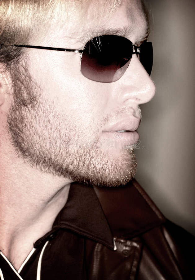 Man and sunglasses. Blond haired man looking off into the distance with sunglasses and leather jacket stock image