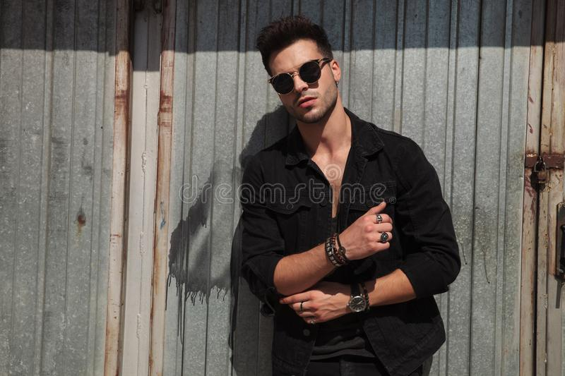 Man with sunglasses fixing his sleeves near metal door royalty free stock photos