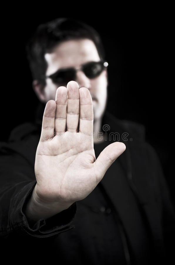 Man in sunglasses holds up hand royalty free stock photos