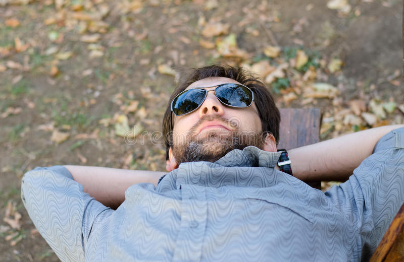 Download Man With Sunglasses Lying On Bench Stock Image - Image: 27785143