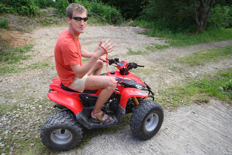 A man in sunglasses on a quad bike ride royalty free stock images