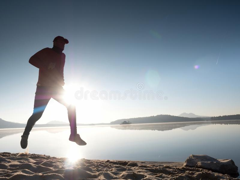 Man with sunglasses, red baseball cap and red black sportswear is running and exercising on beach. stock photos