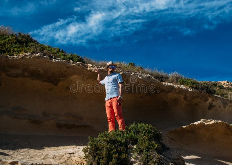 Man in sunglasses and red trousers staying in the hills royalty free stock image