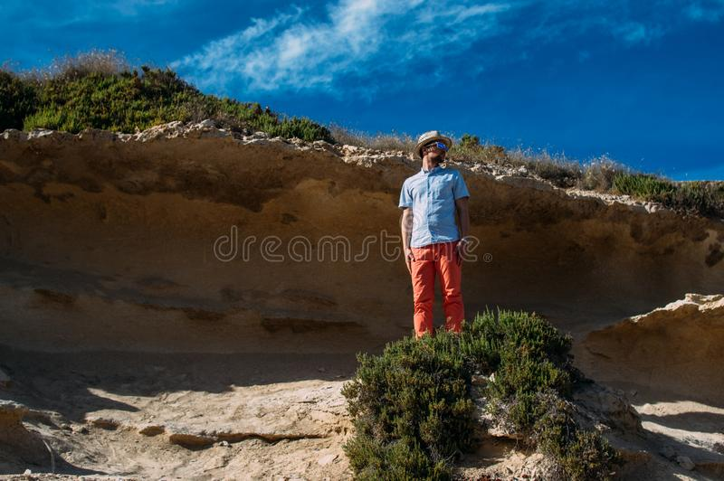Man in sunglasses and red trousers staying in the hills royalty free stock photo