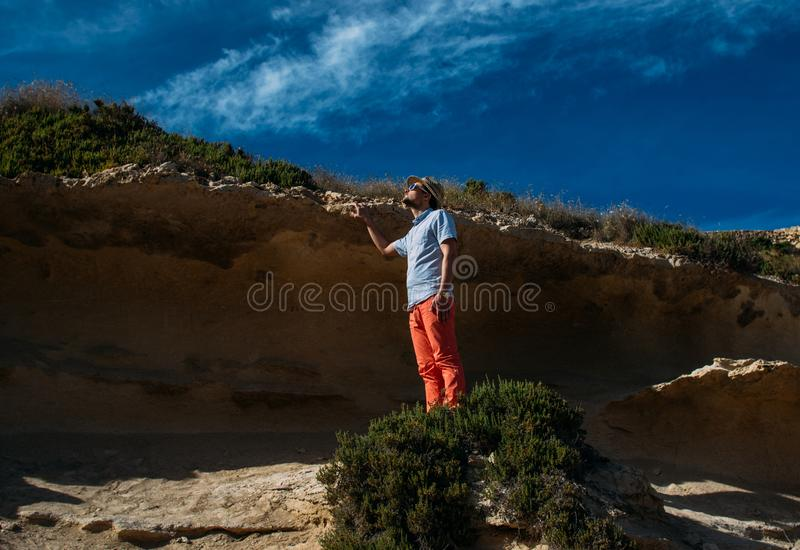 Man in sunglasses and red trousers staying in the hills royalty free stock photography