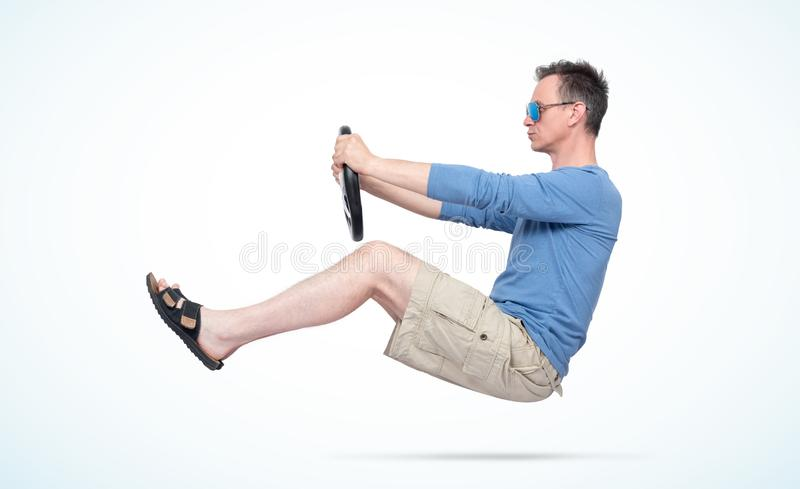 Man in sunglasses, shorts, blue t-shirt and sandals drives car with a steering wheel, on light day background. Auto driver concept stock photos