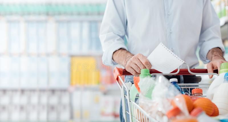 Man shopping with a grocery list. Man at the supermarket shopping with a grocery list and pushing a full cart, lifestyle and retail concept stock photography