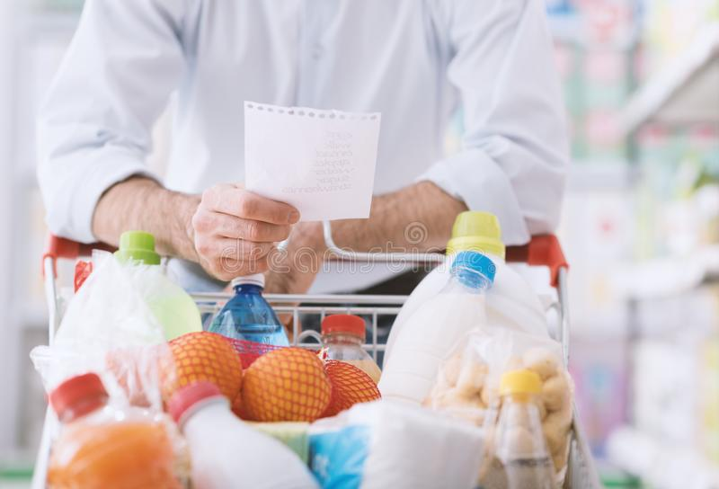 Man shopping with a grocery list. Man at the supermarket shopping with a grocery list and pushing a full cart, lifestyle and retail concept royalty free stock photo