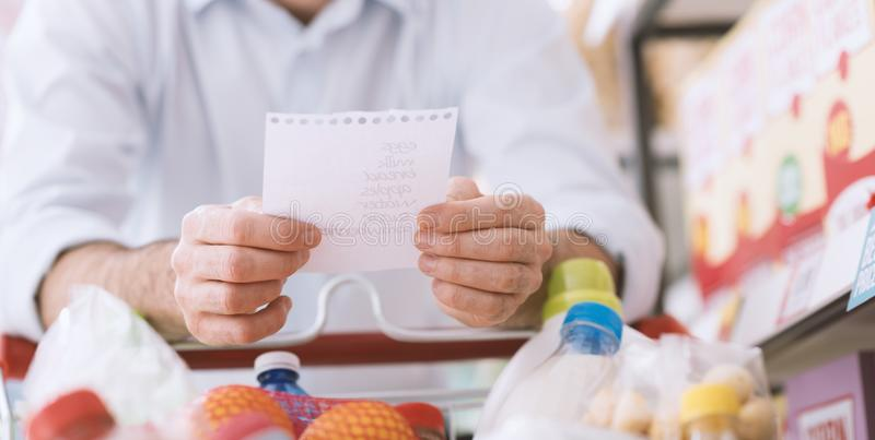 Man shopping with a grocery list. Man at the supermarket shopping with a grocery list and pushing a full cart, lifestyle and retail concept stock images