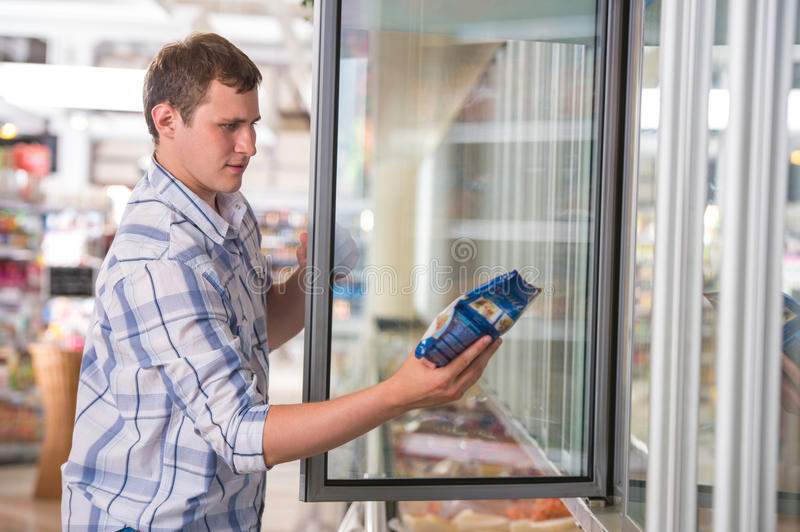 Man in a supermarket standing in front of freezer. Man in a supermarket standing in front of the freezer looking for his favorite frozen food royalty free stock images