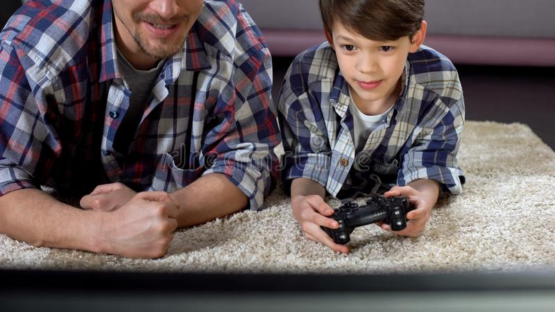 Man supporting his little son playing video game at home, family relationship stock photos
