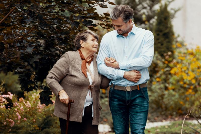 Man supporting weak senior woman with walking stick in the garden stock photo