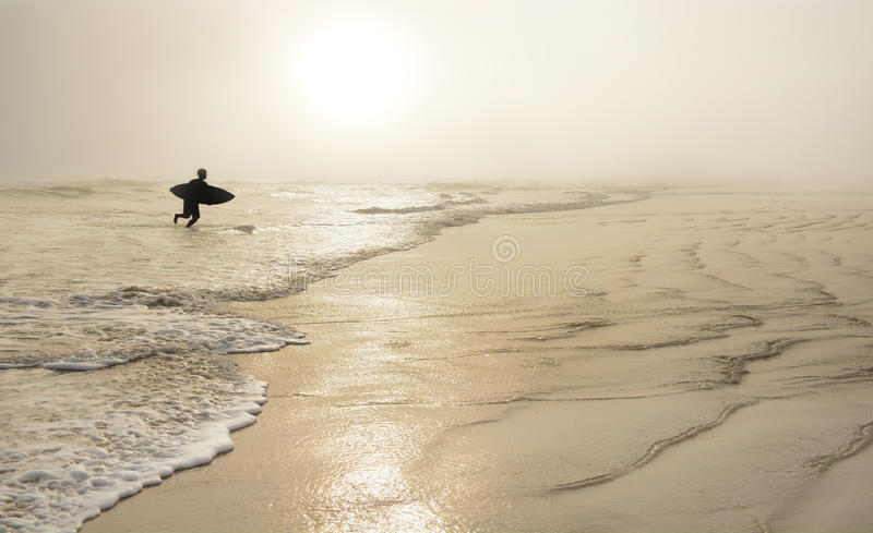 Man with surfboard on the beautiful foggy beach. Boy running with surfboard on a golden beach at sunrise. Daytona Beach, Florida stock photo
