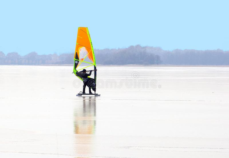 Man ice surfing skating lakes Loosdrechtse Plassen, Netherlands. Man is surfing on frozen lake Loosdrechtse Plassen at a cold winter day, Loosdrecht, Netherlands stock photos