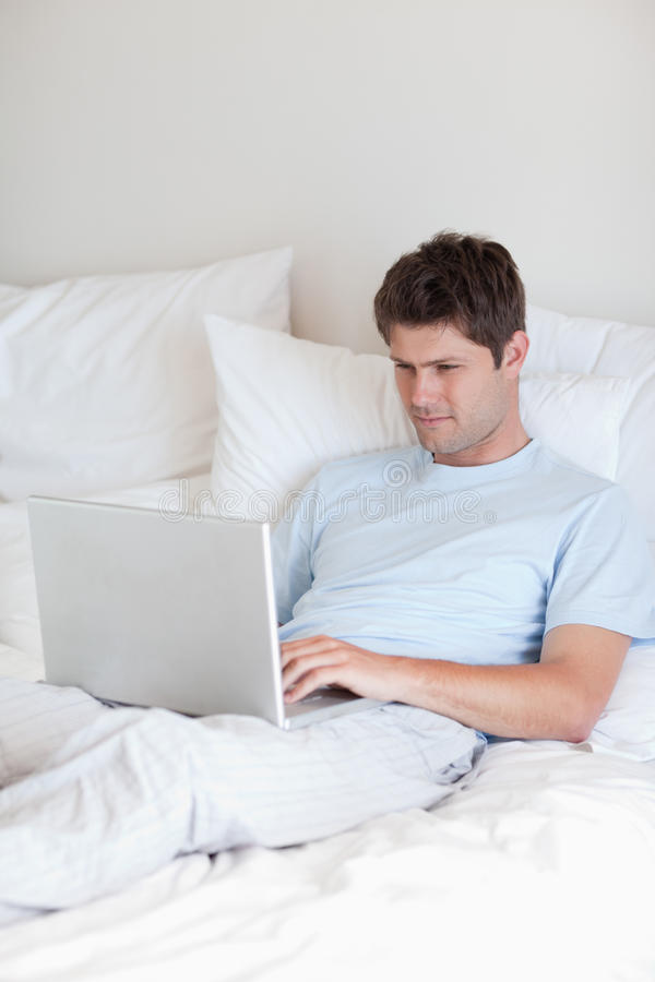 Man surfing the internet in bed royalty free stock photography