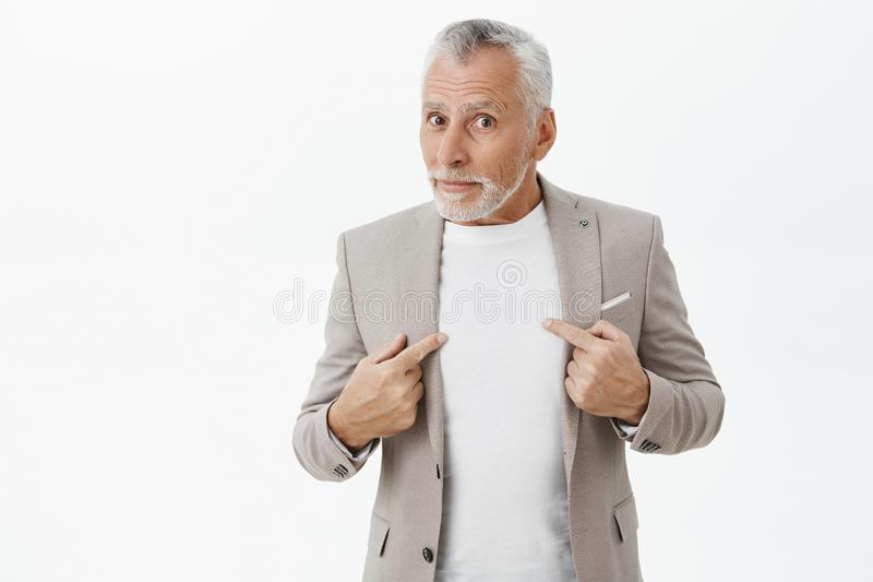 Man surprised and questioned being picked by boss standing unsure over grey wall in elegant formal suit pointing at royalty free stock photo