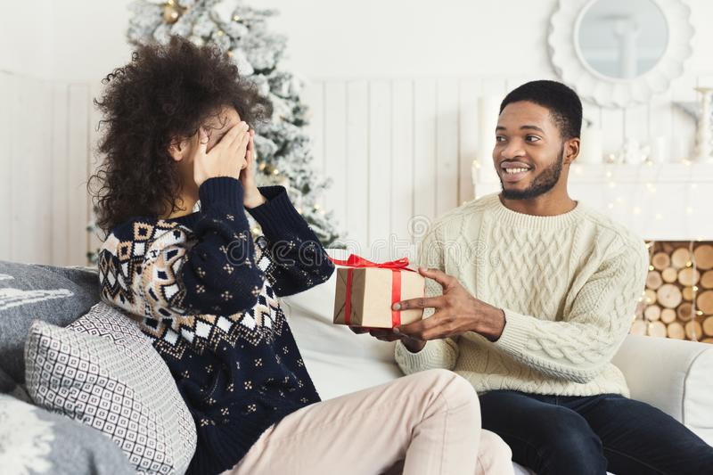 Man surprising girl with Christmas present royalty free stock photography