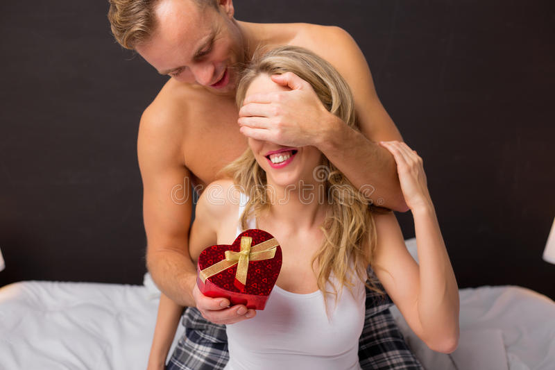 Man surprising his girlfriend in bed with gift stock photo
