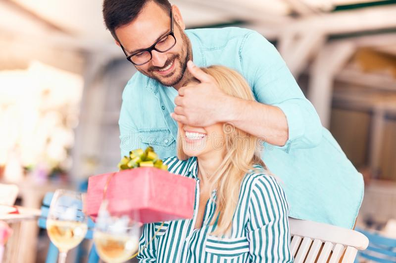 Man surprising his girlfriend with a gift. Surprise stock image