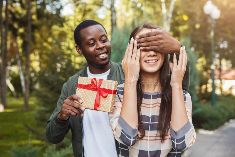 Man surprising his girlfriend with gift royalty free stock photography