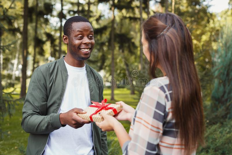 Man surprising his girlfriend with gift royalty free stock photo