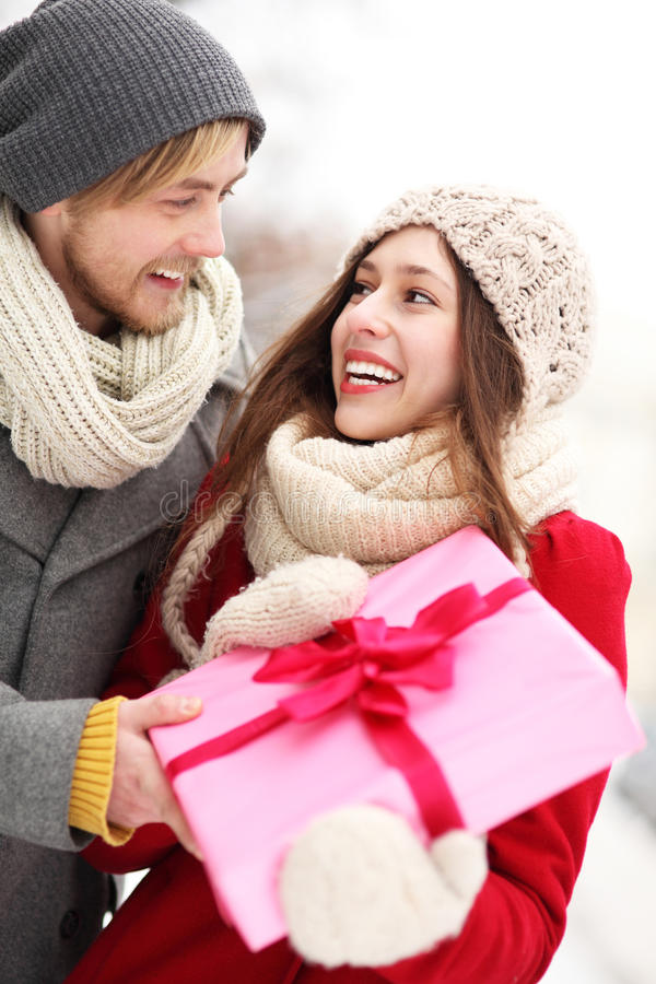 Man surprising woman with gift. Young Couple in Winter Clothes stock photos