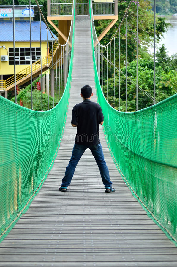 Man on the suspension bridge. Watching to next side royalty free stock image