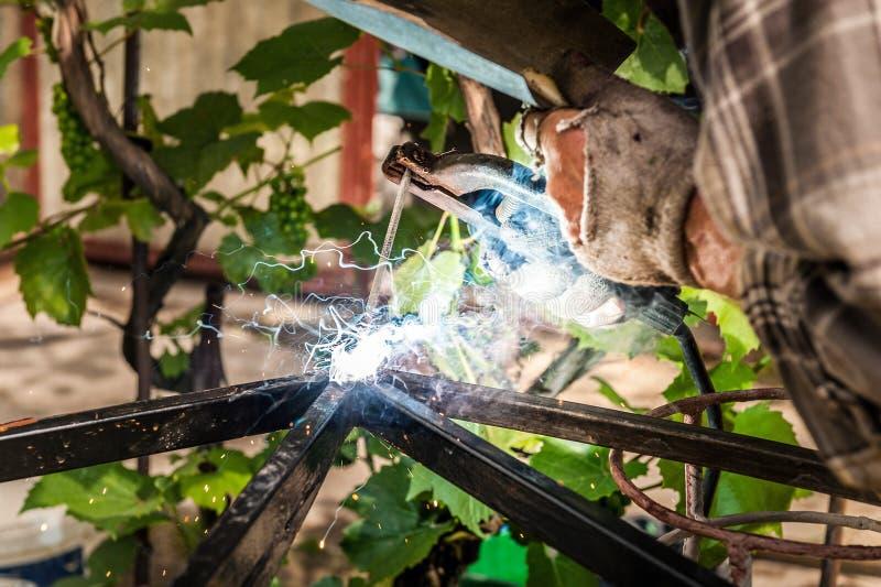 Man svetsning i skyddande kugghjul på hans trädgård royaltyfri bild