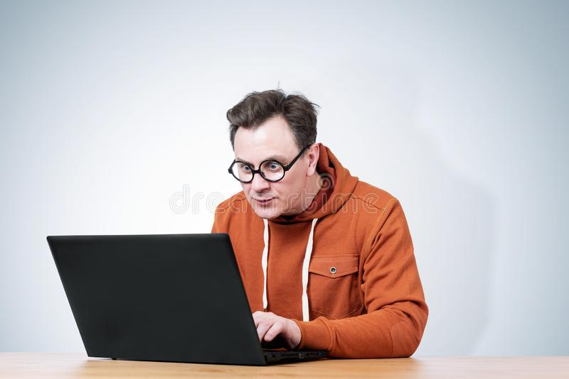 Man  in a sweatshirt and round glasses sits at a table and works with a laptop royalty free stock images