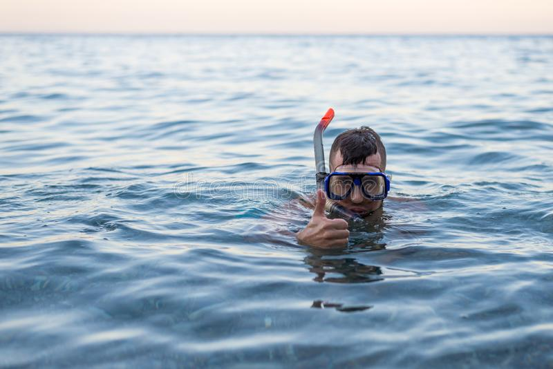 Man swiming in a mask for diving and showing a sign approx stock photos