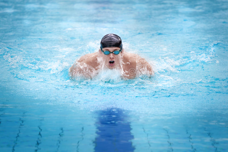 Man swimmer in cap taking breath. Swimmer in cap breathing performing the butterfly stroke stock photos