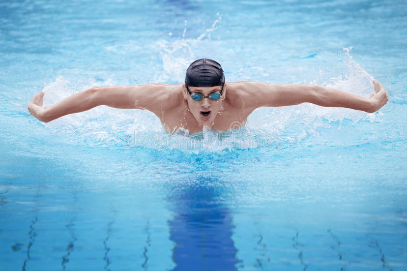 Man swimmer performing the butterfly stroke. Swimmer in cap and goggles breathing performing the butterfly stroke royalty free stock photo