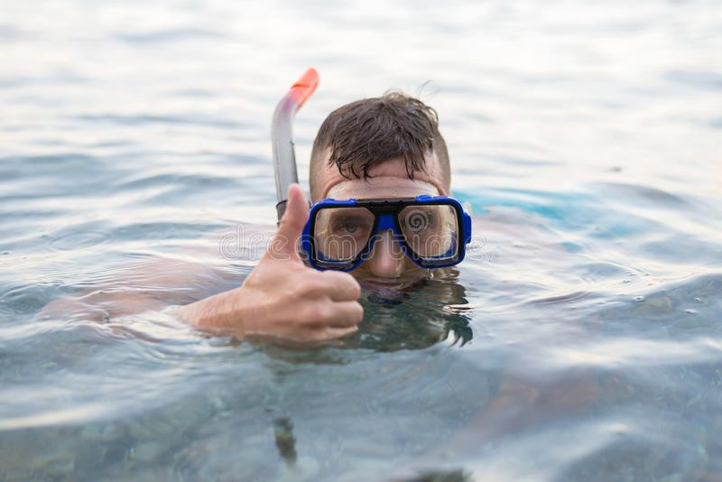 Man swimming in a mask for diving and showing a sign approx royalty free stock photos