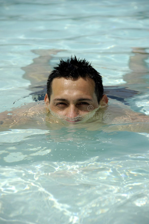 Man in swimming pool. A man resting in a swimming pool royalty free stock photos